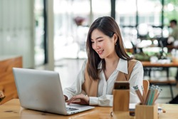 Beautiful young asian woman sitting at coffee shop using laptop. Happy young businesswoman sitting at table in cafe with tab top computer.
