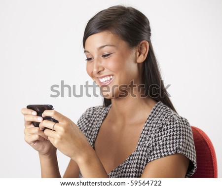 Beautiful young Asian woman smiles while writing a text message on her mobile phone. Horizontal shot.