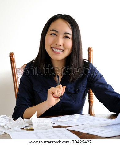 Beautiful young Asian woman smiling as she works on her tax returns - thinking of a refund.