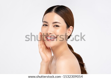 Photo of  Beautiful young Asian woman smiling with hand touching face isolated on white background for beauty and skin care concepts