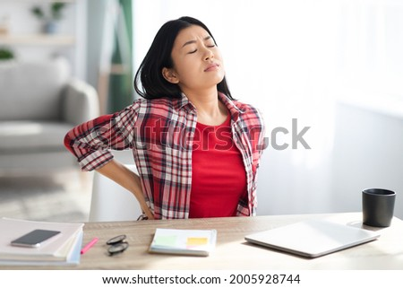 Beautiful Young Asian Woman Suffering From Backache While Sitting At Desk In Home Office, Tired Korean Freelancer Lady Having Acute Lower Back Pain After Long Time Working With Laptop Computer Foto stock ©