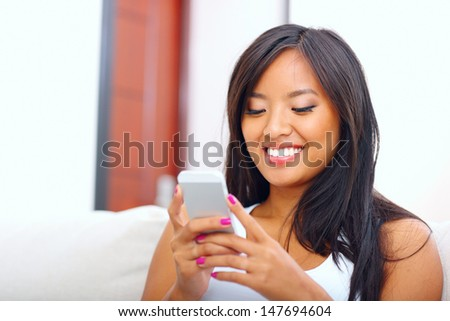 Beautiful young asian woman text messaging with her smart phone at home