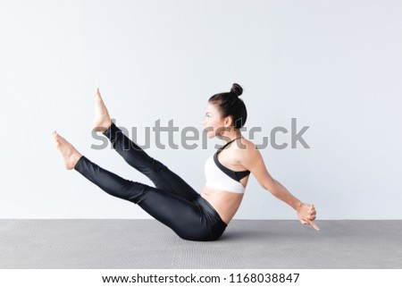 Beautiful young asian woman wearing sportswear practicing yoga in studio,natural light.Concept : yoga poses for beginner.Seated yoga variation.Legs straight.