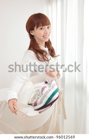 Beautiful young Asian woman with a laundry basket at the window