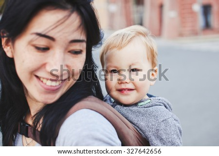 Beautiful young asian woman with freckles and her son relax outdoors. Mother brunette with dark hair and her son is blond. Unusual appearance and heredity concept. Baby sits in sling on mothers back