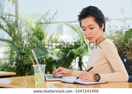 Beautiful young Asian woman working on laptop in cafe and checking notes in planner stock photo
