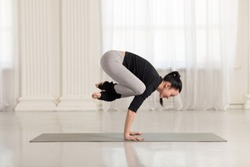 Beautiful young asian woman working out indoors, doing yoga exercise on gray mat, handstand asana, exercise for arms and wrists strength, Crane Crow Pose, Bakasana.