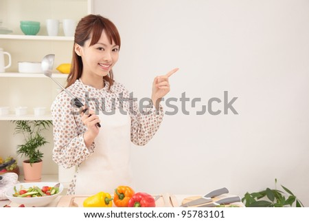 Beautiful young Asian women point to the text space in the kitchen