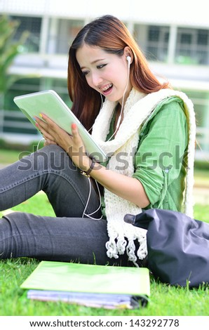 Beautiful young asian women student learning with computer tablet