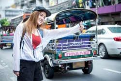 beautiful Young Asian women tourist traveler smiling with backpack on the Traffic Road raising hand calling cab in China town Yaowarat city bangkok thailand . girl waiting for a taxi car bus,tuk tuk