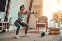 Beautiful young athletic girl in leggings and top crouches with dumbbells at home. Sport, healthy lifestyle.