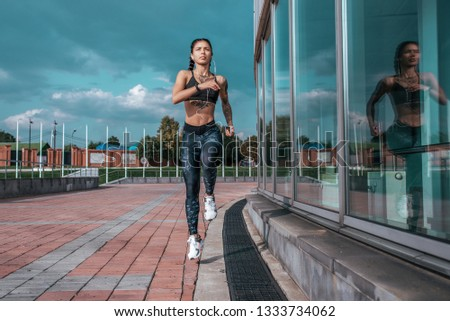 Beautiful young athletic girl tattoos runs morning for jog fitness training, sportswear, leggings top. Phone listens music headphones. Summer city workout. Background sky glass windows. High jump. #1333734062