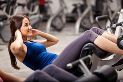 Beautiful young athletic woman doing some crunches in a bench at the gym