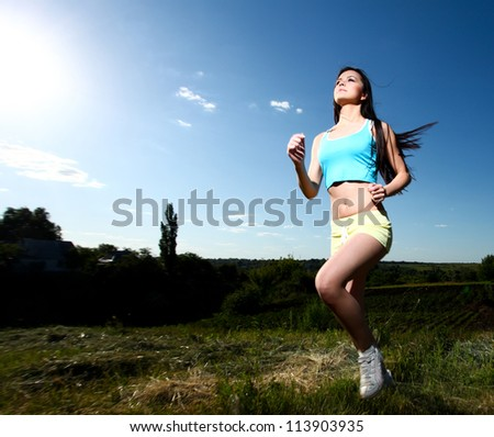 Beautiful young athletic woman running through the green grass against the blue sky