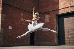 beautiful young ballerina jumping and dancing on urban street