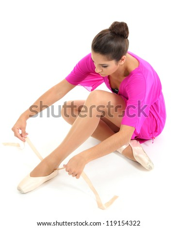 beautiful young ballerina puts on pointe isolated on white