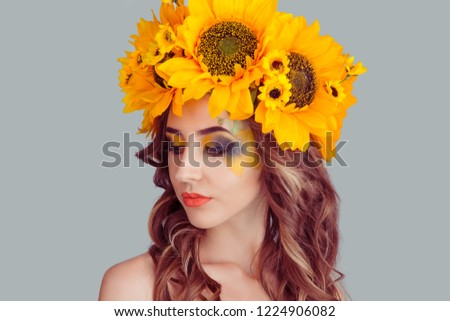 Beautiful young beautiful woman beauty model with yellow sunflowers head floral headband eyes closed looking down shows makeup posing looking down isolated on gray background. Spring style concept. #1224906082