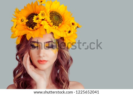 Beautiful young beautiful woman beauty model with yellow sunflowers head floral headband eyes closed looking down showing artistic makeup posing isolated on gray background. Summer style concept. #1225652041