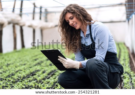 Beautiful young biotechnology woman engineer with clipboard and pen, examining plants for disease in greenhouse with apron and gloves. Greenhouse produce. Food production.