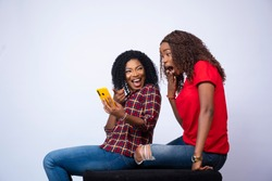 beautiful young black lady showing her friend something exciting on her phone