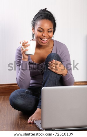 Beautiful young black student girl, big smile, sitting on the floor at home, using her laptop to communicate with friends.