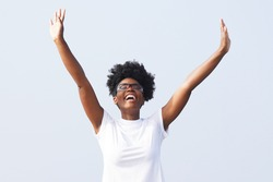 Beautiful young black woman celebrates outdoors with her hands in the air and wearing sporty glasses against a background of blue sky