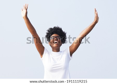 Beautiful young black woman celebrates outdoors with her hands in the air and wearing sporty glasses against a background of blue sky                               Сток-фото ©