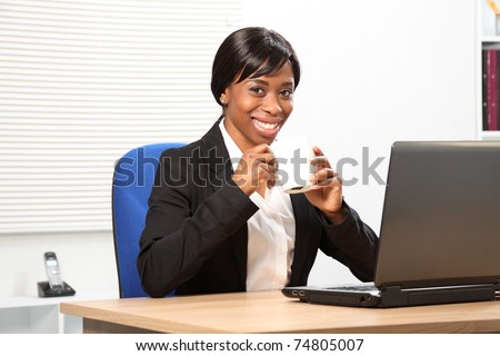 Beautiful young black woman enjoying her coffee while working in the office.