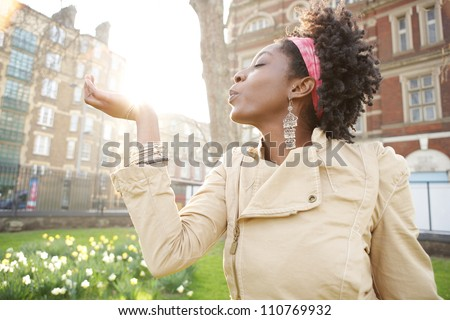 Beautiful young black woman holding the sun in her hand at sunset while visiting London city.