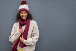 Beautiful young black woman in winter clothing standing against grey wall. Portrait of attractive african woman wearing woolen cap and scarf and looking at camera. Smiling girl on gray background.