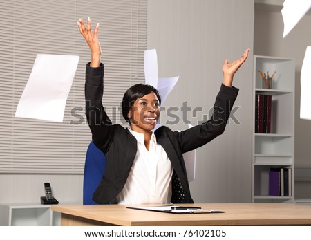 Beautiful young black woman working in office throws a load of papers into the air in happiness. She has a beautiful smile.