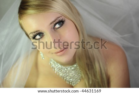beautiful young blond girl in a wedding dress getting ready for wedding