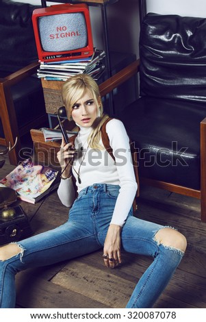 Beautiful young blond girl wearing cowboy clothes and posing like a doll. She is captured in nice scene with old TV, phone, furniture, magazines, table, pictures, dartboard and fen.  Stock photo ©