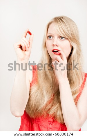 Beautiful young blond girl with pill or tablet