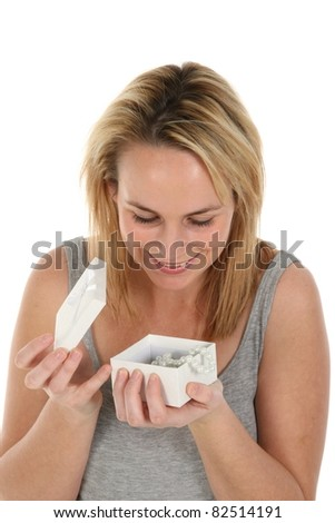 Beautiful young blond lady opening a box with gift of string of pearls