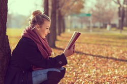 Beautiful young blond leaning on a tree on an autumn day, reading a book