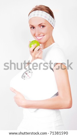 beautiful young blond sporty woman  holding scales  and eating a green apple