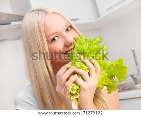 beautiful young blond woman eating salad in the kitchen at home #71279122