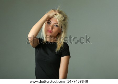 Beautiful young blond woman in a black T-shirt on a gray background. pretty blonde touches her hair