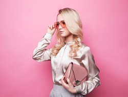 Beautiful young blond woman in a blouse wearing glasses, holding handbag.