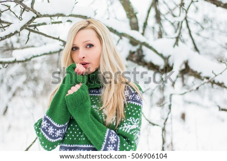 Beautiful young blond woman is dressed in a warm green sweater with Norwegian patterns on the snowy background in winter forest. Girl blowing on hands to warm up. Christmas theme