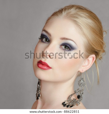 Beautiful young blond woman portrait against dark gray background