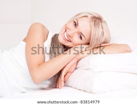 beautiful young blond woman relaxing on the bed at home