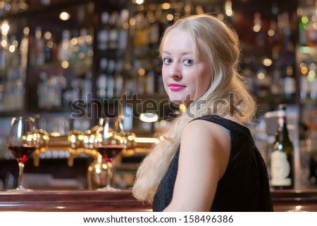 Beautiful young blond woman seated at a bar counter in an upmarket in a hotel, club or restaurant looking back over her shoulder at the camera