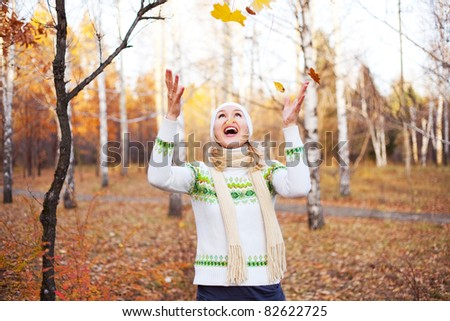 beautiful young blond woman spending time in the park and catching maple leaves