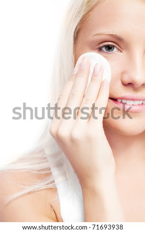 beautiful young blond woman using cotton pads at home