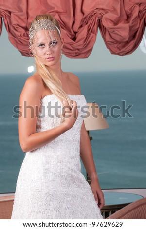 beautiful young blond woman wearing long white dress posing