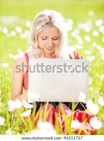 beautiful young blond woman with a laptop  in the park  on a warm summer day