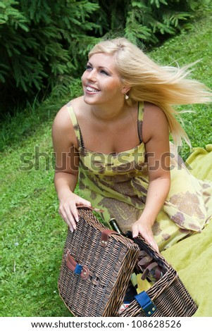 Beautiful young blond woman with picnic crib outdoor