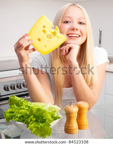 beautiful young blond woman with salad and cheese in the kitchen at home